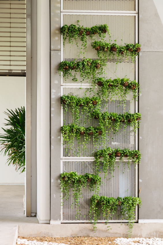 13-vertical-garden Hanging flower pots from fencing, particularly in areas not typically thought of as fodder for adornment, frees up extra space while sprucing up what may be a boring area.