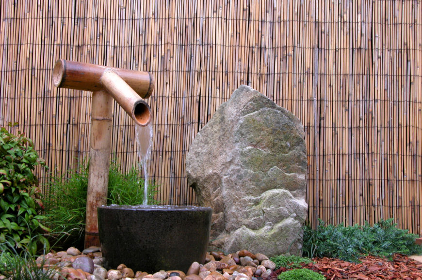 Bamboo is at its most beautiful when placed as a decorative fence around a traditional Japanese Zen garden. This particular fence acts as a backdrop to a water feature and mossy stone.