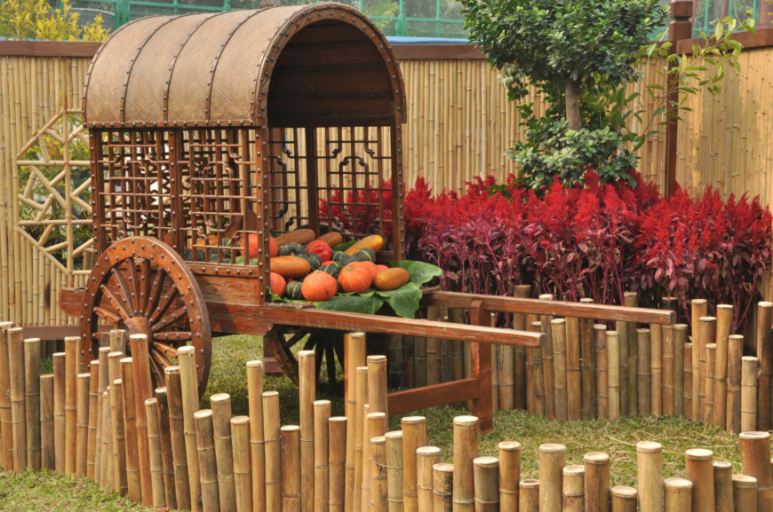 This is an example of a different design, with tall bamboo shades and stalks pressed into the ground to form a tall edging around a vegetable cart. The tall panels of the fence are occasionally interrupted by octagonal cutouts with a beautiful, simple design.