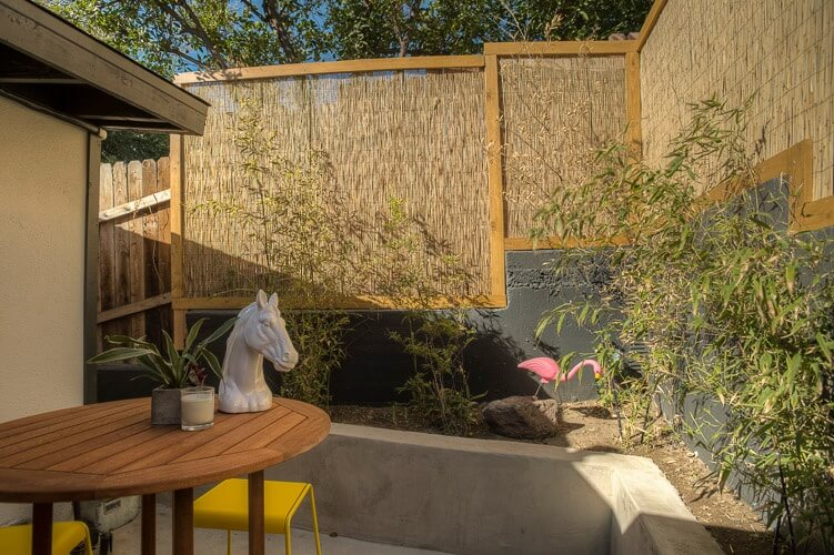 While we can see that as the fencing stretches towards the front of the home, it transitions from reed bamboo on concrete supports to a wooden privacy wall. The planting beds are raised as well, creating a sunken patio area.