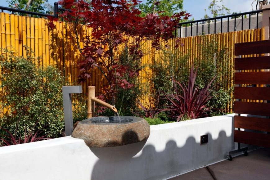 Another double-layered fence, with a natural thick bamboo privacy fence supported by a taller black wrought iron security fence. A sunken planting bed is decorated by a lovely bamboo fountain with a stone basin.