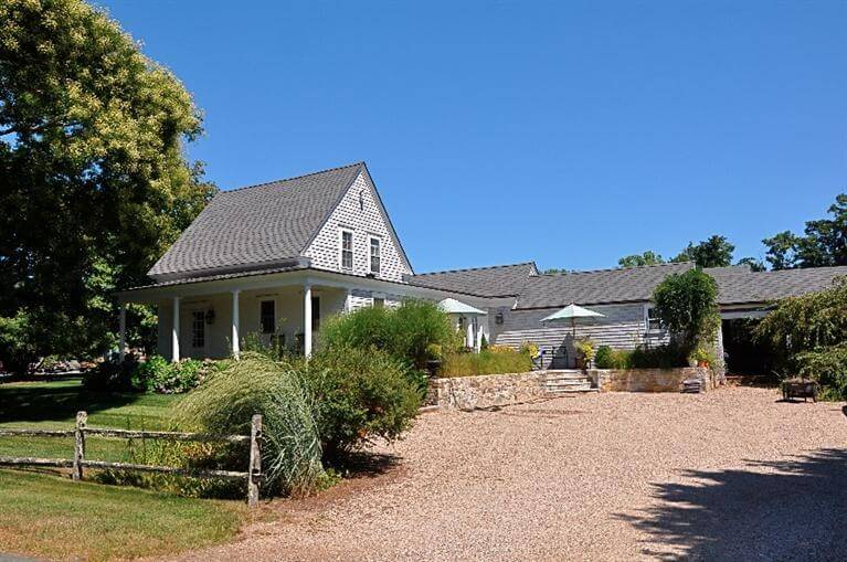 A simple farmhouse with low maintenance landscaping including a well aged split rail fence no more than 3 feet high.