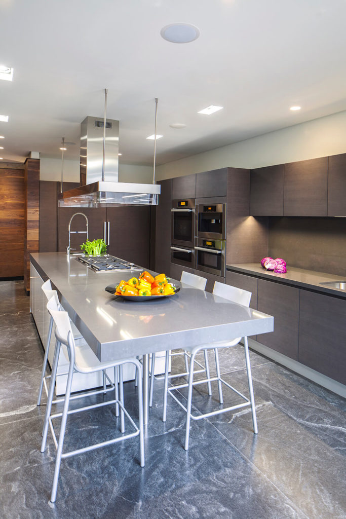 Seen from the opposite side, we can better take in the rich flooring and sleek cabinetry that inform the kitchen space. The glossy countertop of the island extends into a full in-kitchen dining space.