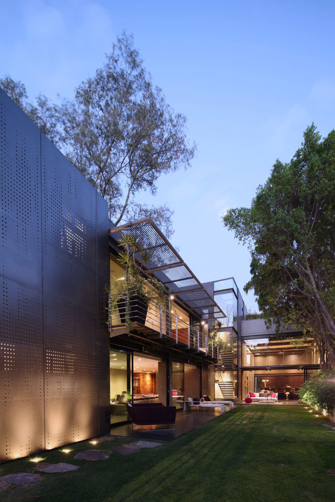 Across the immaculate lawn, we can see into the various living room spaces, connected in an almost uninterrupted flow between indoors and out. The glass covered facade facilitates this striking, open design.