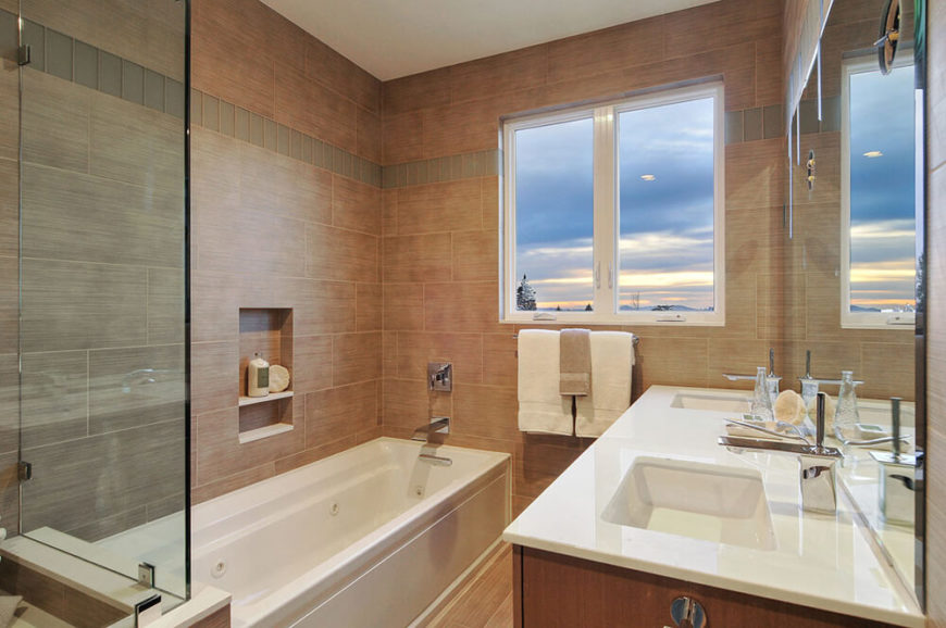 The bathroom matches the warm neutral tone of the bedroom, with tile walls matching the color tone of the hardwood flooring. Sleek bath and vanity components emphasize a modern look without overt styling.