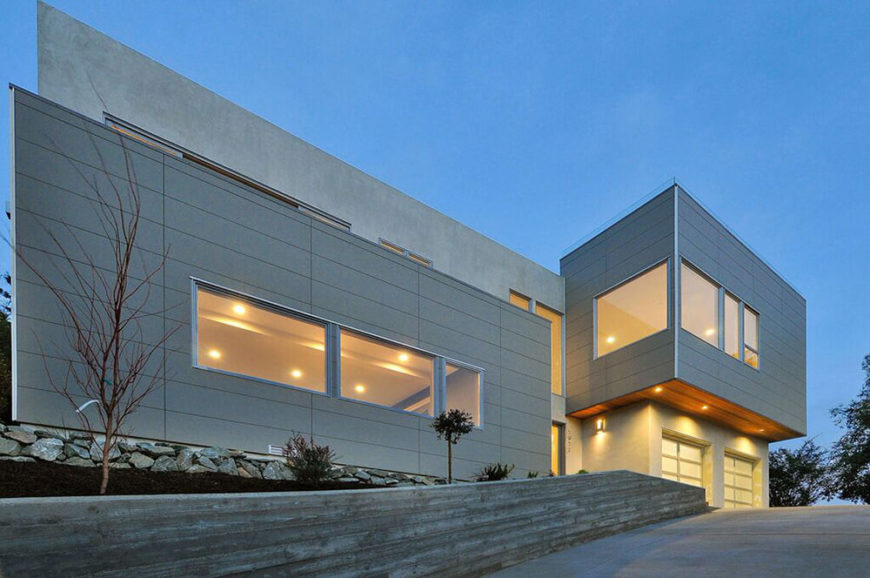 The sharp edged, angular design stands out on its sloped landscape at night, with large windows offering glowing views into the large interior. The home is bordered by a small natural rock wall, as seen at left.