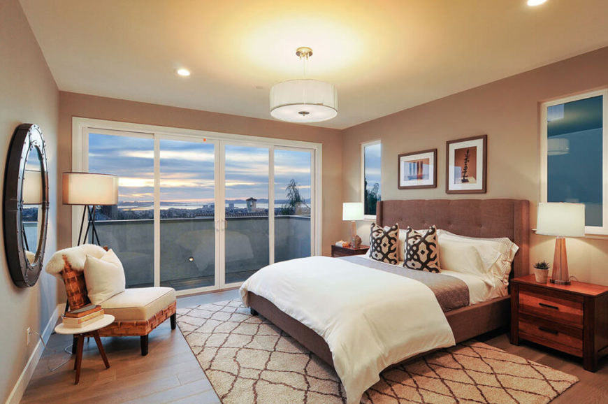 The primary bedroom enjoys expansive views courtesy of a set of large sliding glass doors. The hardwood flooring in here grounds the neutral space, pairing well with the dark natural wood dressers and chair.
