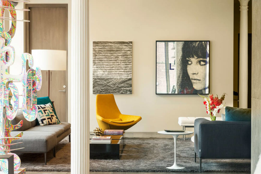 The living room features bold pops of yellow and a colorful, abstract sculpture.