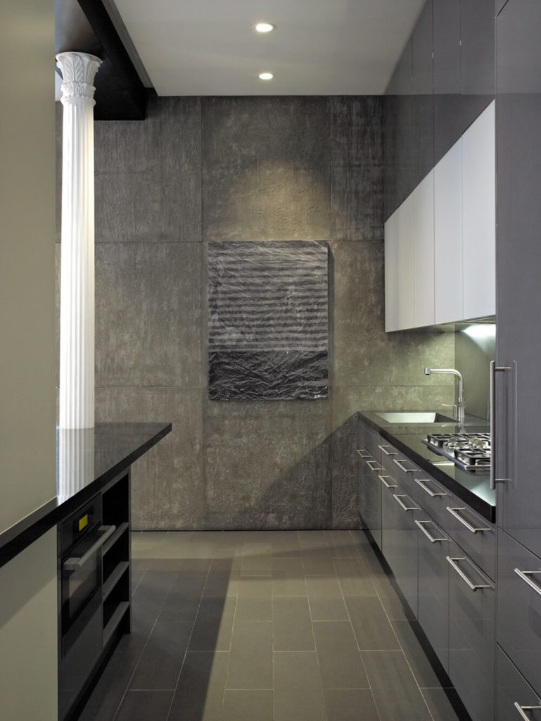 The kitchen is long and narrow, done up in a monochromatic color scheme with sleek, stainless steel accents. The wall are breaks up the texture of the rough concrete with a ridged and wrinkled appearance.