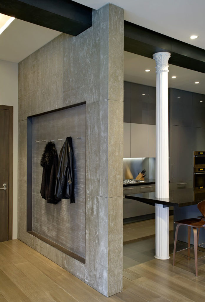 Coat hooks supply a place to hang your coat as you enter into the loft. Just around the corner you can see into the kitchen and one of many contrast pillars supporting the space while also breaking it up visually. Concrete walls create a textural juxtaposition to the wood floors.