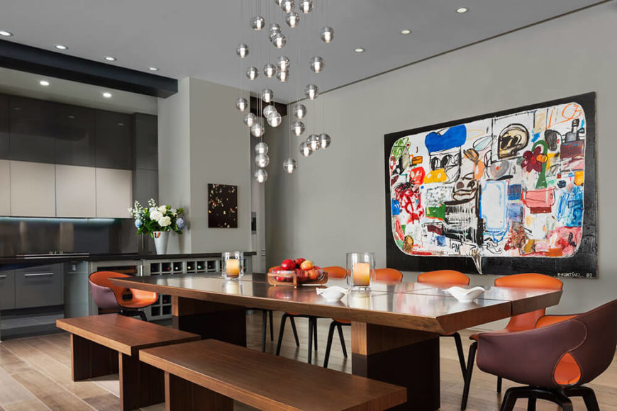 Bold and colorful artwork adorns the wall and acts as the focal point of the large space. Warm textures of wood and leather help to combat the grand scale of the loft, bringing it down to a more human scale.