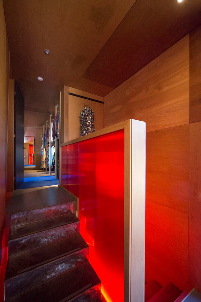 The staircase flaunts a bit of industrial toughness as well as a burst of candy red coloring, making for a unique focal point within the home. To the left we can see the bedroom and related spaces.