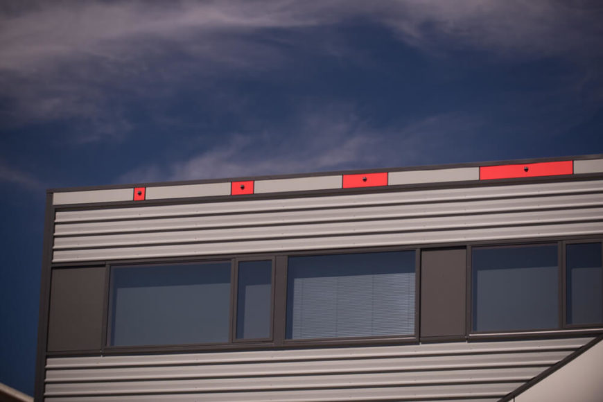 Small but important details abound on the exterior, including these tiny patches of bright red in increasingly lengthy segments, running directly below the roofline.
