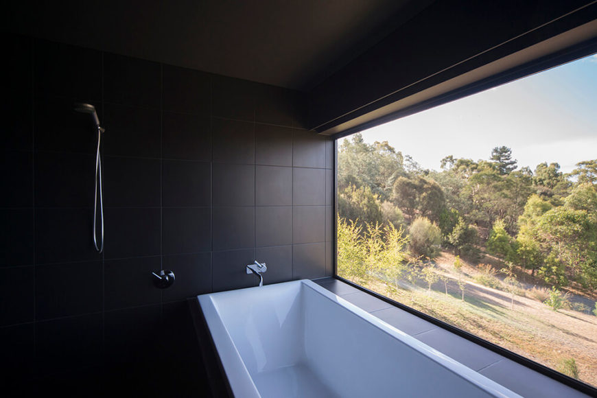The bathroom is all sleek black tiling, centered on a massive angular soaking tub. The huge picture window to the right provides expansive views for anyone relaxing in the tub.