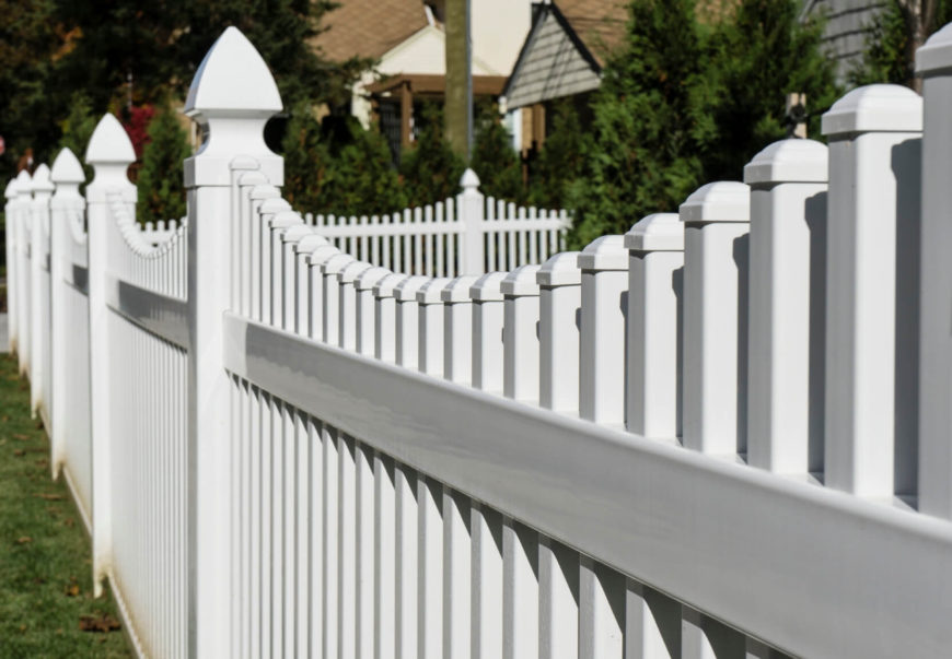 A close up of a vinyl fence, showing the details on each cap and the sleek finish. Picket fences are a common design style in suburban areas.