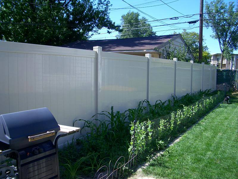 A sleek white privacy fence with rows of plants in front of it. The height of the fence is such that no nosy neighbor could peer over.