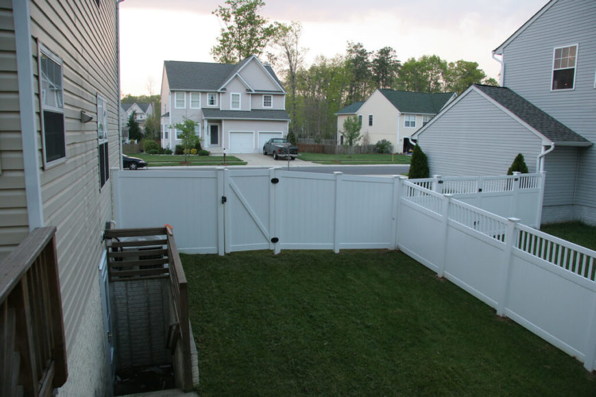 A residential vinyl fence with a gate leading to the front yard. The side of the fence shared with the neighbor has a decorative border at the top.