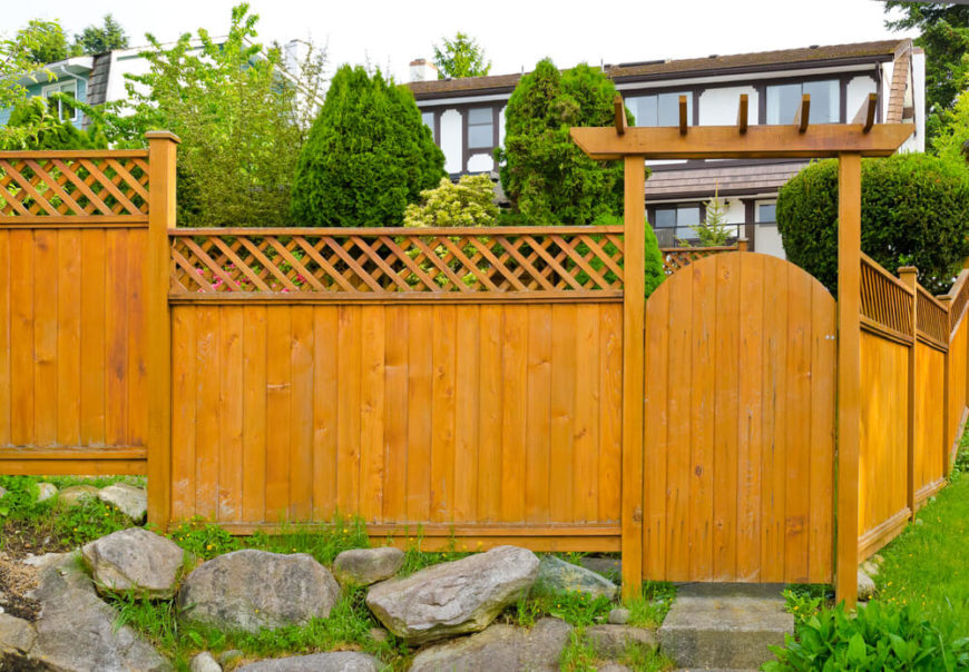 This tall wooden privacy fence with lattice top and gate provides a good deal of privacy.