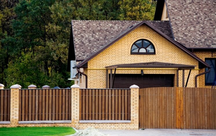 Here's a tall privacy fence with a large car gate. Mixed with a brick structure, this fence is given a bit more stability.