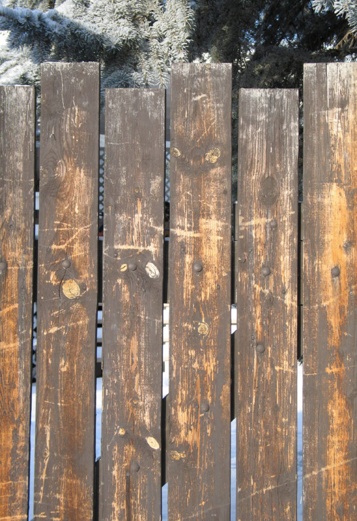This unfinished wood fence with different sized components has a rough and rugged look.