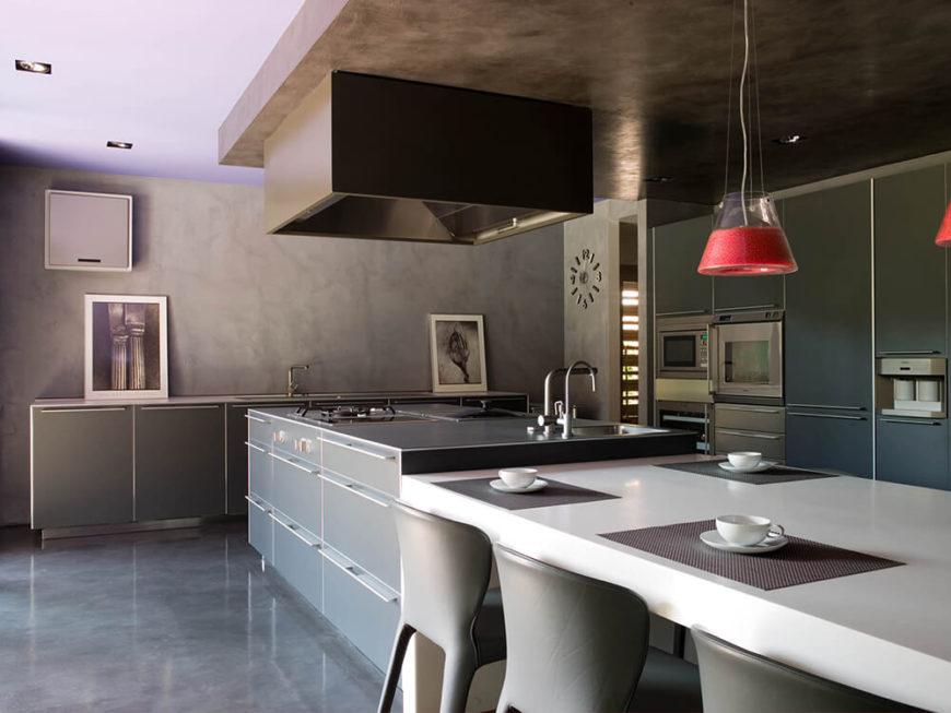 The kitchen, by contrast, features a more sedate color palette, with muted greys, whites, and stainless steel defining the space. The massive kitchen island features a built-in range and sink, with an extension that becomes an in-kitchen dining table in white.