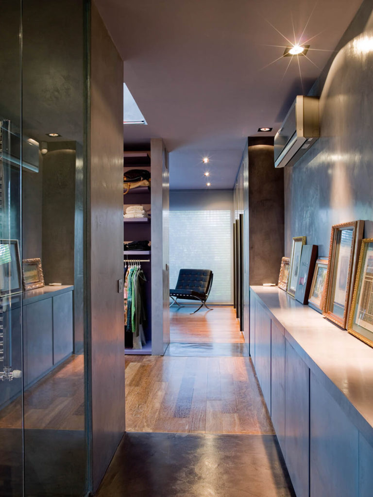 Upstairs, we come to the more private areas of the home, with an open hall connecting the large closet and display area with the primary bedroom. This space is lined with cabinetry and a lit display shelf for artwork.