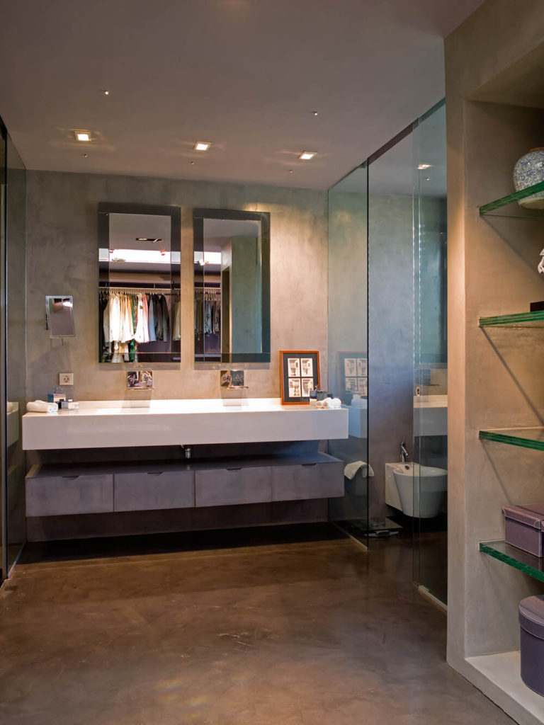 The primary bathroom is awash in varied materials, with glass panels separating the water closet and walk-in showers from the main area, and a lengthy floating white vanity over grey storage cabinetry.