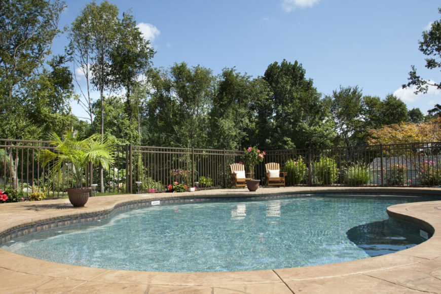A tall iron bar fence surrounds this pool area, separating it from the garden and yard.