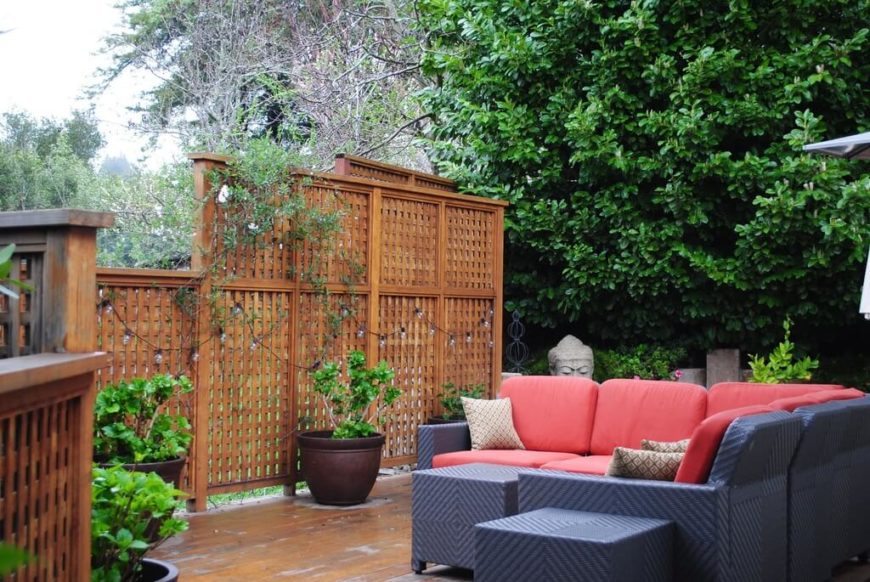 This is a large finished wooden lattice design. This screen was built as part of the patio, making it one cohesive piece with the corresponding landscaping.