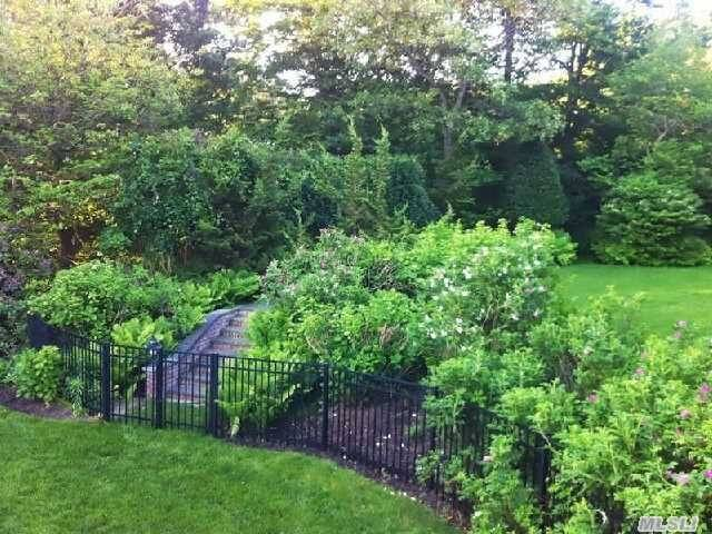 A slim wrought iron fence surrounding a lush and verdant garden. A gate stands before the stone steps.