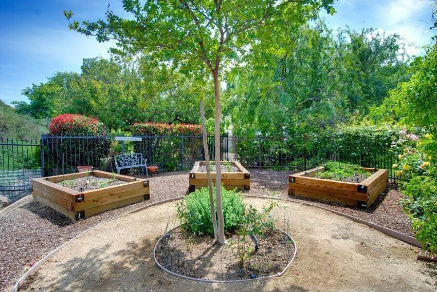 A spiked wrought iron gate surrounds this lovely seating area complete with planting boxes and a center tree.
