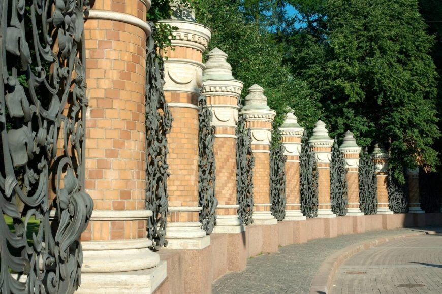 A very ornate wrought iron pattern between brick pillars.