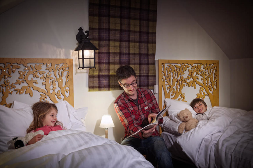The carvings seen on the stairs and throughout the house are seen again in the children's bunk room, as well as the green and purple plaid window coverings.