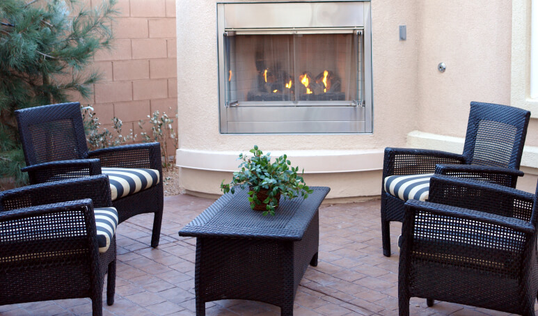 This elegant patio fireplace is attached to the main home, creating a small bump out. The fireplace is screened in, preventing any crackling or popping embers from escaping.