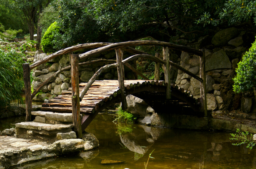 A much more rustic bridge with a high arch above a crystal clear, shallow creek.