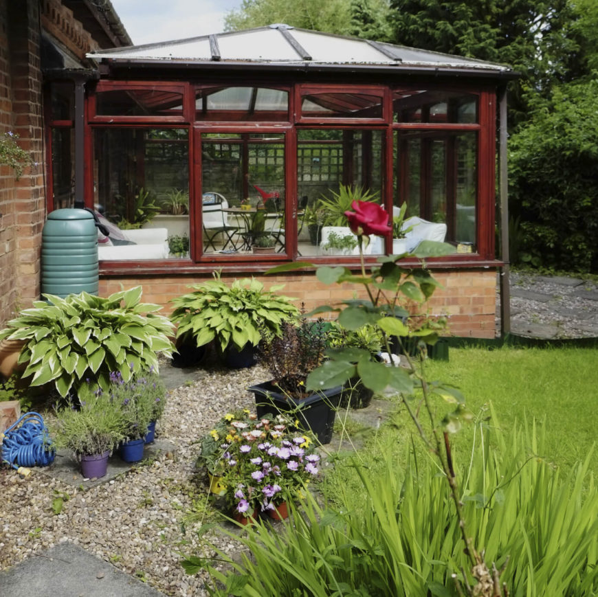 This greenhouse has been combined with a sunroom for a conservatory feel. The building is attached to the rear of the house and is accessible from either the yard or from inside the home.