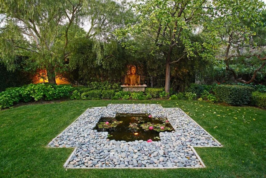 This garden is filled with shrubs and bushes and has a small shrine to one side. At the center is a small pond surrounded by stones.