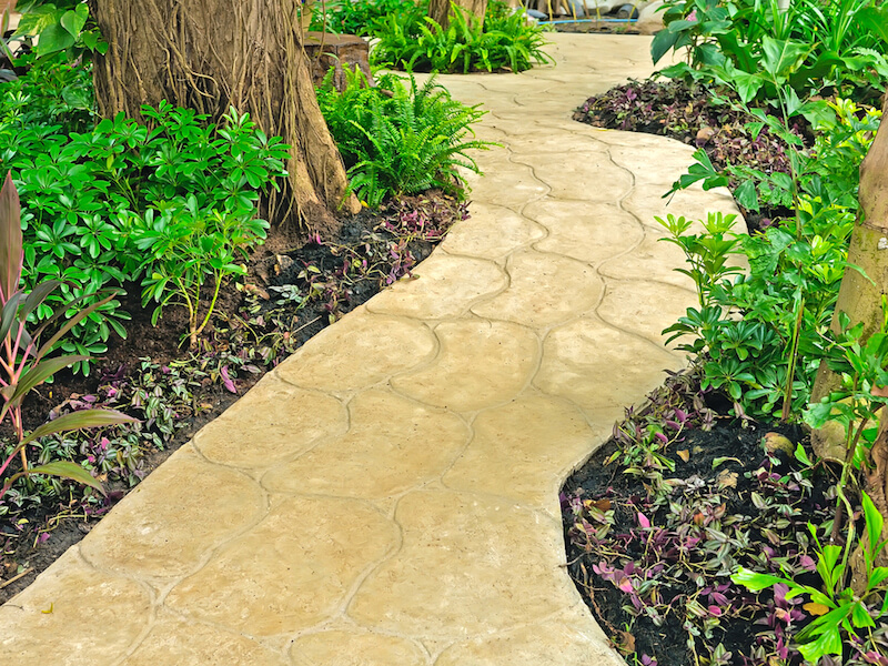 This lovely and subtle stone pathway winds its way through a more forested garden with large, mature trees.