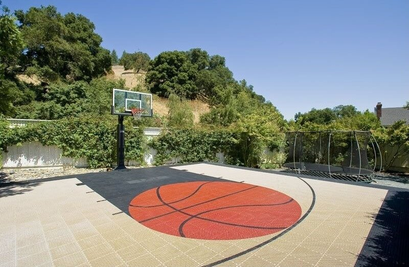 This custom basketball court has a custom tile work basketball decal at the very center.