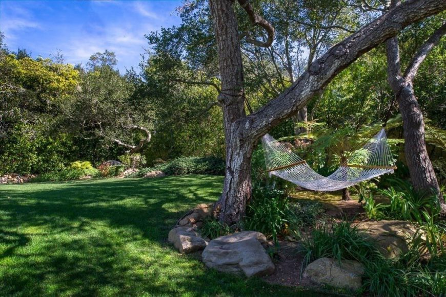 This hammock is strung between two mature trees in the middle of a planting bed marked by rocks.