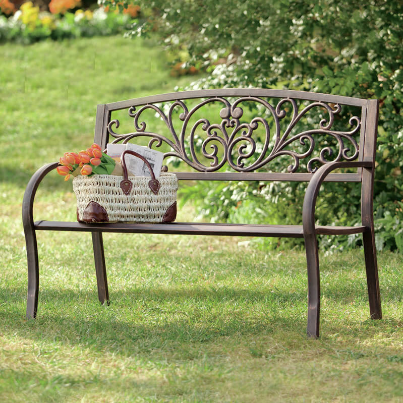 An elegant wrought iron bench with scrollwork decorating the backrest. This piece is perfect for any patio area or garden.