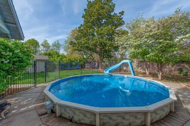 This round above ground pool is surrounded by a concrete pool area, and adorned with a slide. A wrought iron bar fence divides this area off from the rest of the yard.