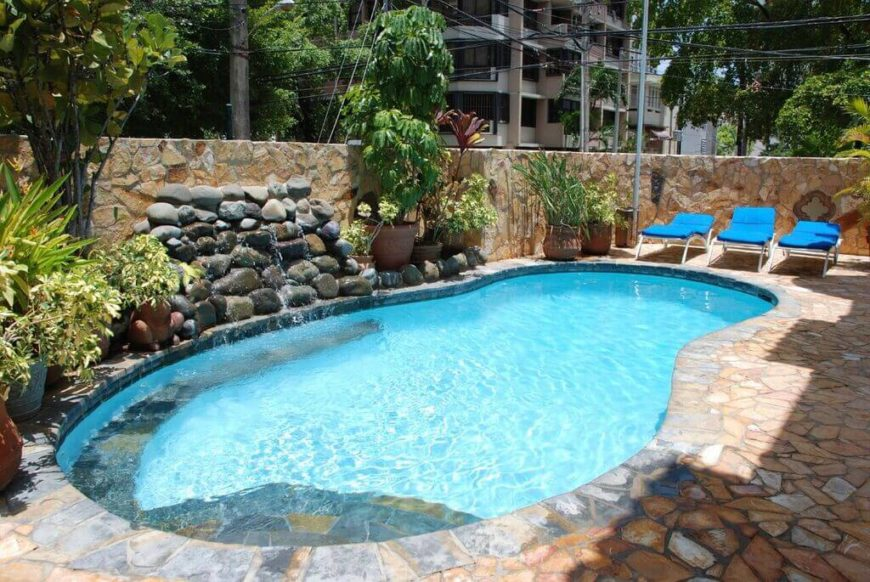 This is a classic example of a small figure eight pool, with a nice stone waterfall, and some potted plants, making a cool landscaped look. This whole pool area is fenced off by a brick wall.