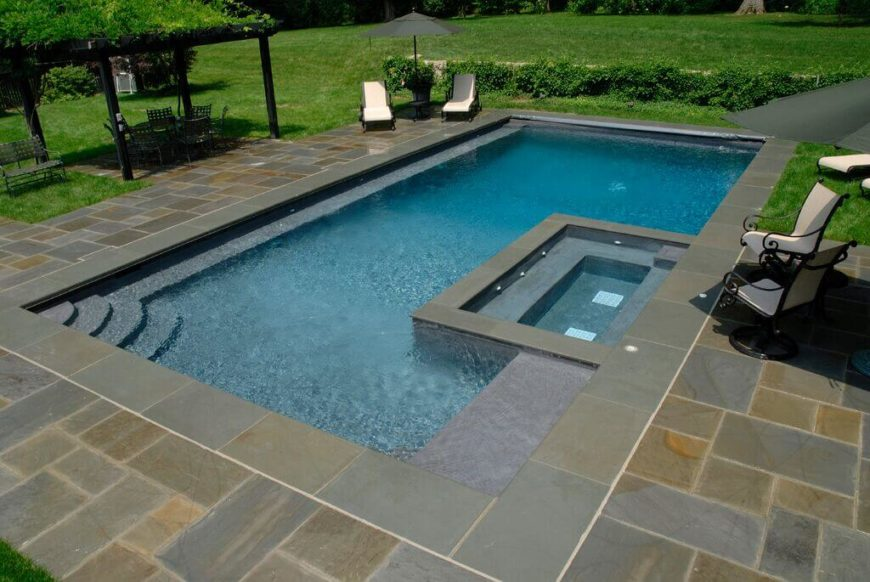 A rectangular pool with a small cutout for a hot tub area.