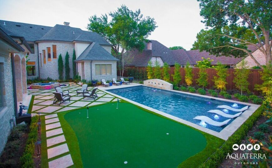 This is a classic rectangular designed pool. The yard uniquely frames it with a small putting green and carefully landscaped greenery.