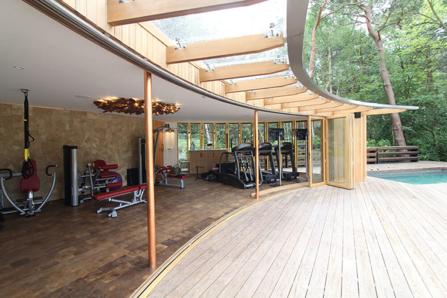 When the glass doors are opened fully, the small home gym is exposed to the decking and breeze. A glass-covered overhang keeps any rain from splashing into the open room.