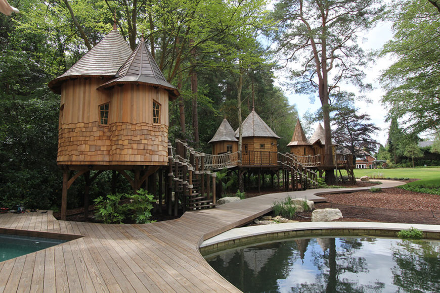 Treehouses near the edge of a swimming pool and a lake.