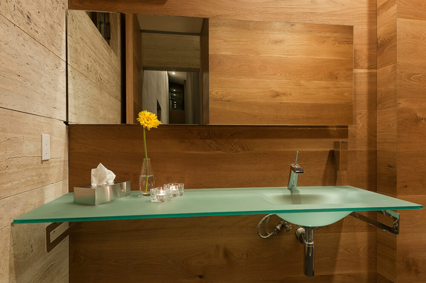 This smaller bathroom is flush with rich wood and marble, with a uniquely striking floating vanity in tempered glass. The integrated sink and frameless mirror emphasize the strong, modern aesthetic of the home.