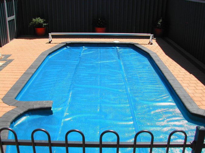 This is a solar cover on an odd shaped pool. many covers can be custom fitted to your specific needs. This pool also has a crank on the far end, for reeling in the cover with ease.