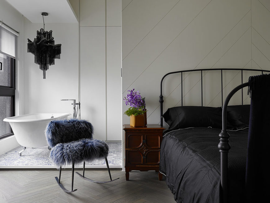 The bed is backed by a free standing feature wall, dividing the sleeping area from the open bathroom behind it. Dark furniture creates a nice contrast with the bright and open design of the home.